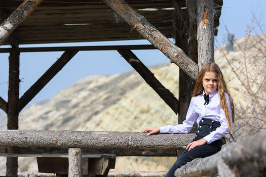 A girl sits on a wooden fence against the background of an abandoned wooden structure