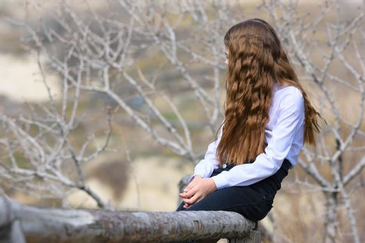 A girl sits on a wooden fence and looks away into the distance