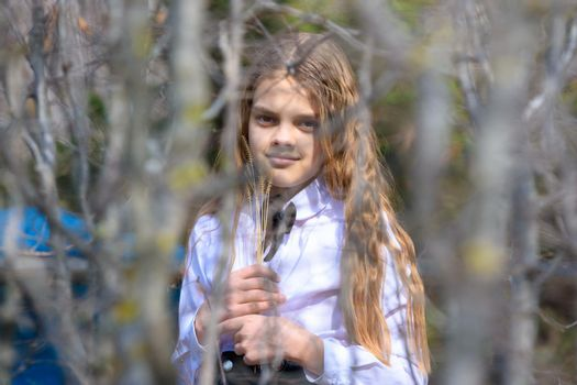A girl stands with dried wildflowers, in the foreground blurred branches of bushes