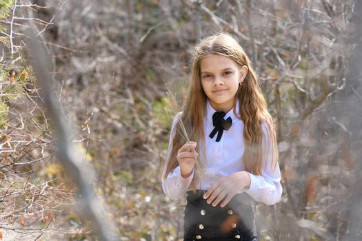 A girl in a white shirt walks through the spring forest and holds several straws in her hands