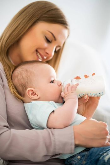 Happy mother is feeding her baby boy at home.