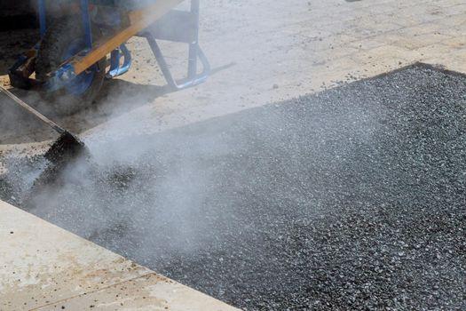 Road worker repair asphalt covering new road surface while laying asphalt