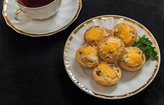 On the plate is delicious tartlets with cheese, next to a Cup of coffee. Presented on a dark background.