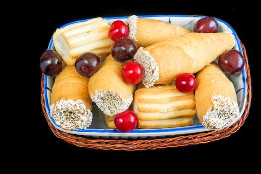 On the napkin on the table ceramic plate with cookies and cherries in a wicker basket. Presented on a dark background.