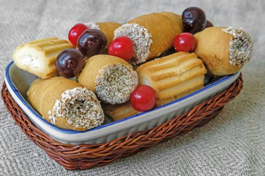 On the napkin on the table ceramic plate with cookies and cherries in a wicker basket.