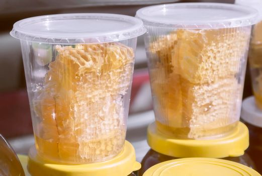 Sold at the fair bee honeycomb with honey in plastic containers.