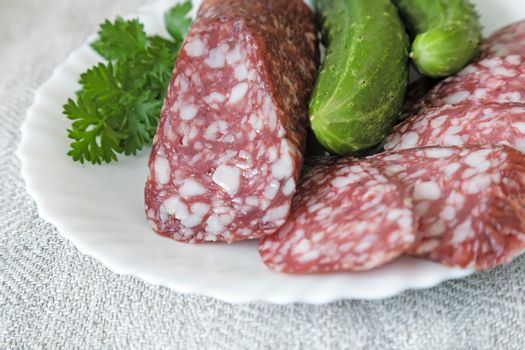 On the tablecloth of the table is a plate of sliced sausages, cucumbers and parsley.