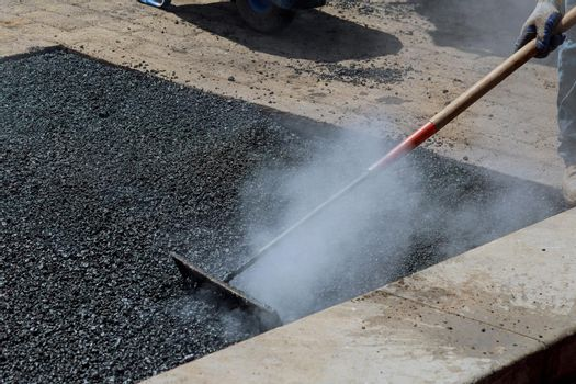 Worker repair asphalt covering while laying asphalt new road surface a man with a special tool