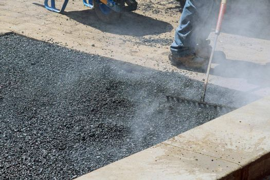 Worker with a special tool takes asphalt mixture a repair asphalt covering while laying asphalt