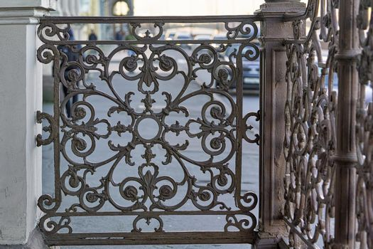 An openwork cast iron lattice adorns the porch of the house