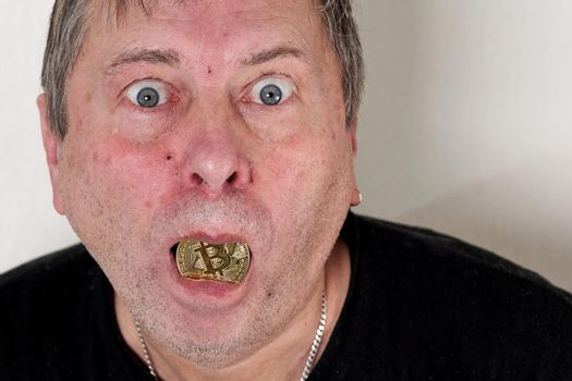 Freak with bulging eyes and bitcoin in his mouth looking at the camera