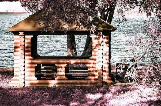 On the river Bank in the shade of the trees, a gazebo made of logs and covered with shingles. The effect of infrared film.