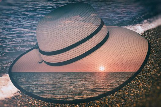 On the seaside women's hat in the rays of the evening sun. The double exposure effect.