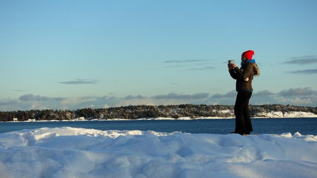 A young woman captures the landscape with her mobile phone on a winter morning in Scandinavia