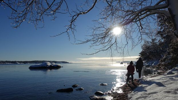 two people walking on a winter day with snow and full sun by the sea in Scandinavia