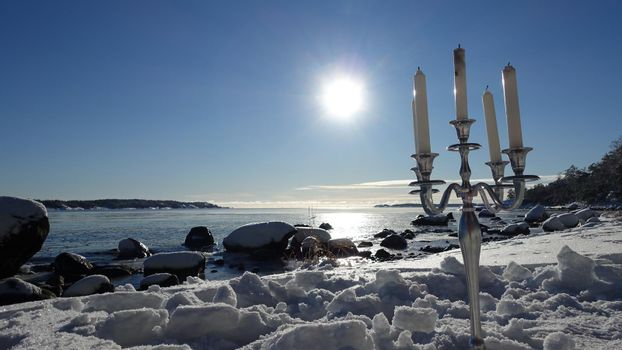 A silver candlestick by the sea on a sunny winter day in Scandinavia