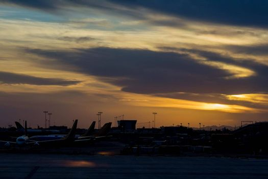 During a wonderful sunset with airport many aircraft lined up on the terminal gate