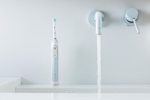 electric toothbrush on a wash-bowl, water flowing from faucet