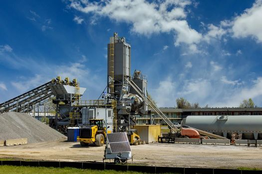 Industrial equipment of a mining and processing plant with a front end loader in the panorama