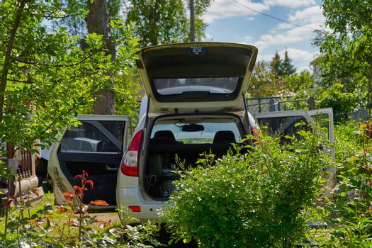 White car with open doors, trunk and hood stands on a garden plot