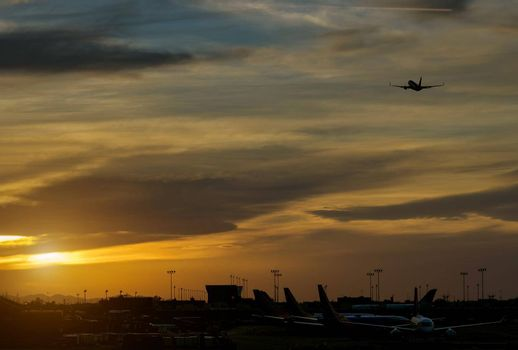 Silhouette of runway signs during sunset the sky red clouds the airport during takeoff in the plane