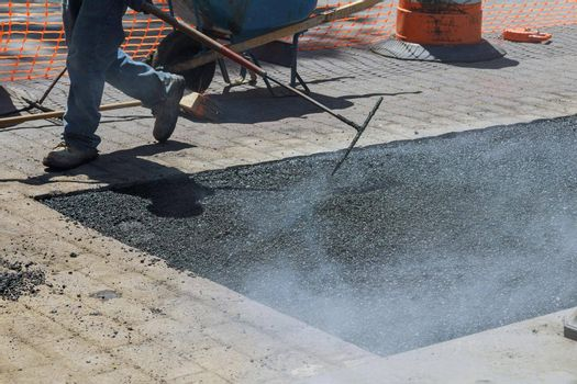 Road with fresh asphalt reconstruction on of worker repair asphalt covering