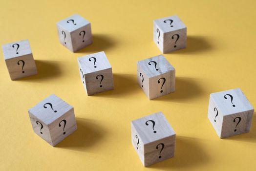 Wooden cube box with question mark on yellow background