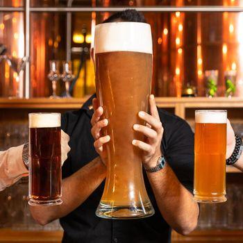 Man holding 3 liter huge beer glass, mug with black, dark beer glasses side by side