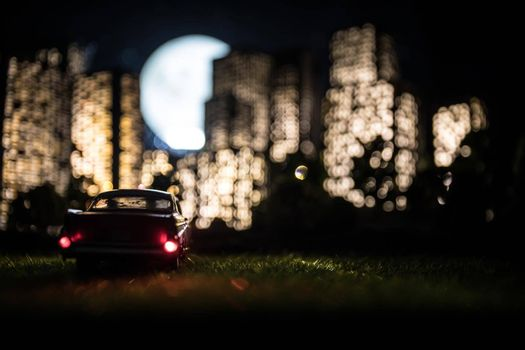 Cartoon style city buildings. Realistic city building miniatures with lights. . Car miniature in front of a night city. Selective focus