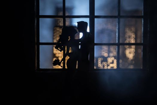 Beautiful view of a miniature city at night from window of dollhouse. Romantic couple at window. Artwork table decoration with handmade realistic dollhouse. Selective focus.