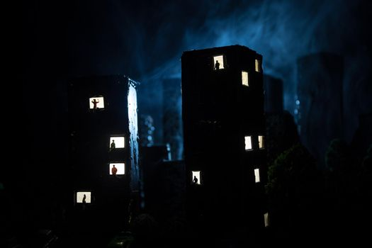 concept of loneliness, in the form of a silhouette of woman and man in a city window at night. Symbol of expectation, dreams and destinies. Creative decoration with City miniature. Selective focus