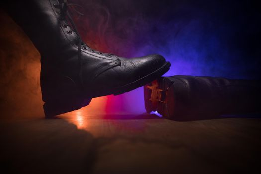 War concept. Old military shoe in a dark toned foggy background. Creative concept of conflict between countries, military aggression. Selective focus