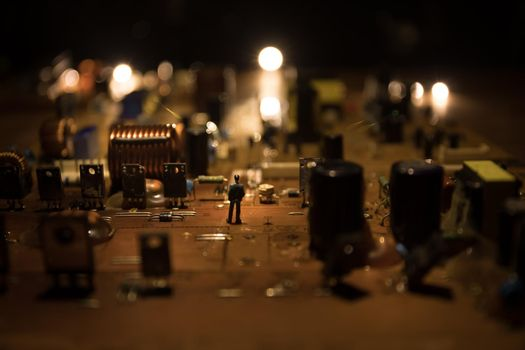 Creative concept of modern technology, inside an electronic device. Man miniature standing on microcircuit. Electronic circuit board close up in low key. Selective focus