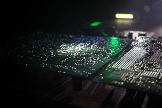 Creative concept of modern technology, inside an electronic device. Electronic circuit board close up in low key. Selective focus