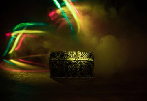 A dark wooden treasure chest with lid closed on wooden table. Selective focus
