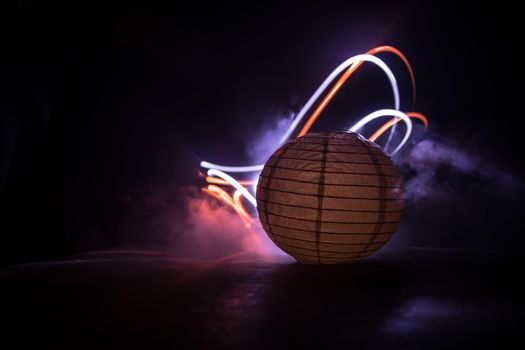 Beautiful paper lantern glowing on wooden table in dark. Selective focus