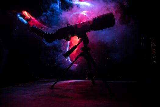 Silhouette of a astronomy telescope on dark foggy backlight. Selective focus