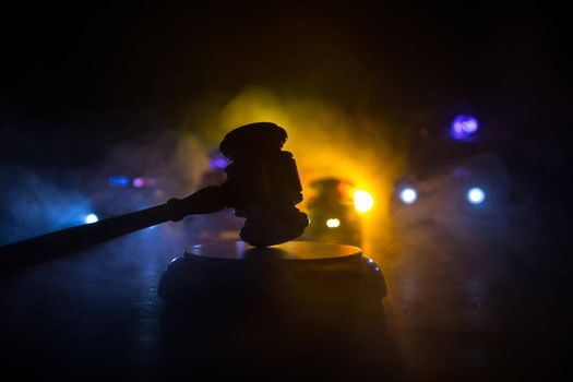 Law theme, mallet of the judge on wooden desk . Silhouette of police cars on backside. Law gavel on dark foggy background with light. Selective focus