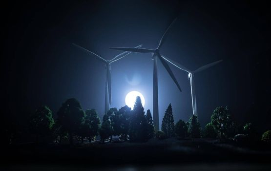 Electricity power in nature or clean energy concept. Wind Turbine producing alternative energy over the forest at night. Creative decoration with small miniature. Selective focus
