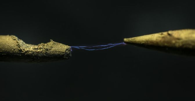 Realistic glowing electricity lightning between two electrodes. Industrial electricity concept. Macro shot