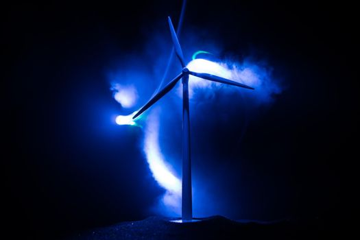 Electricity power in nature or clean energy concept. Wind Turbine producing alternative energy on hill at night. Creative decoration with small miniature. Selective focus