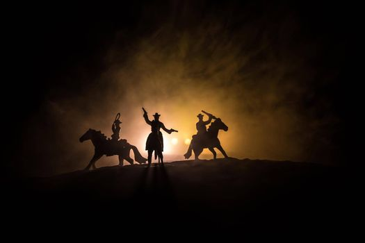 Western concept. Battle between cowboys at night. Duel to the death. Creative artwork decoration on toned foggy background in selective focus