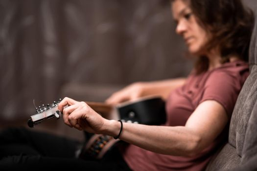 woman tuning guitar at home on the couch