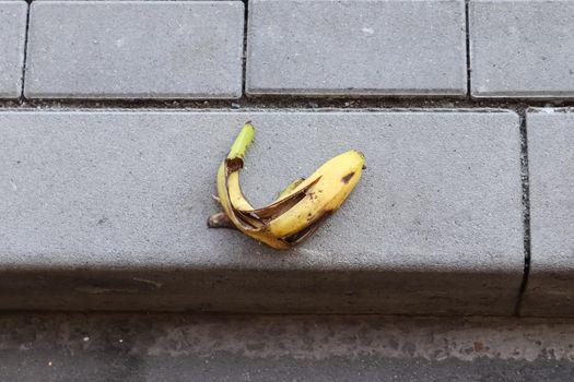 Yellow banana peel on a paved road.