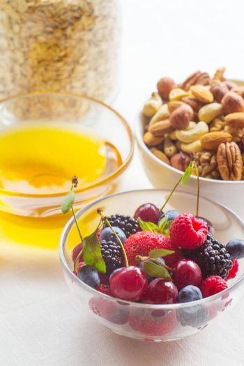 Honey oatmeal, nut and flax seeds granola in a bowl with and fresh berries on white background cereal healthy breakfast concept