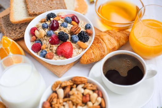 Healthy breakfast with muesli, fruits, berries, nuts, coffee, eggs, honey, oat grains and other close up