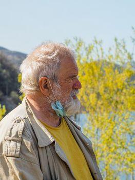 senior man took off the fa mask to breathe outdoors