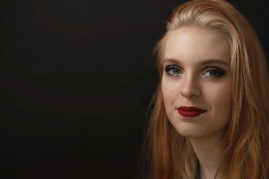 Low key portrait of smiling redhead young woman closeup.