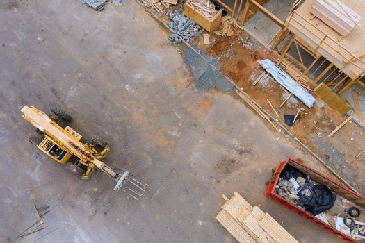Aerial view of forklift stacker wooden boards and trash dumpsters construction on apartment beams framing of a new house under construction