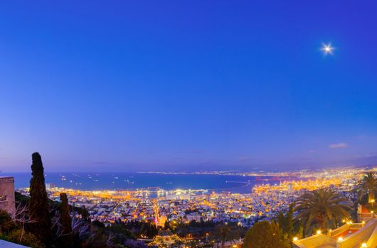 Evening view of Bahai Shrine, gardens, downtown and port, Haifa